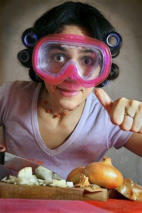 женщина в очках для плавания чистит лук
