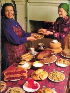 женщины в национальных костюмах у накрытого стола с блюдами пермской кухни