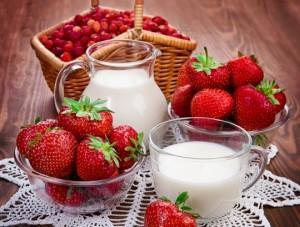 кувшин и стакан с молоком среди ягод клубники