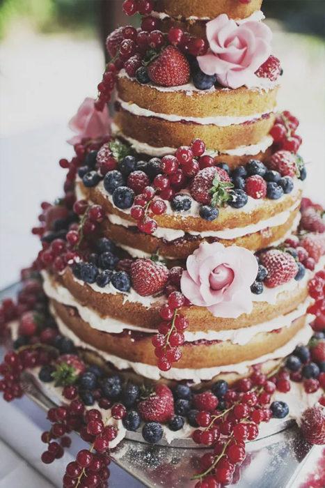 голый свадебный торт украшенный цветами и ягодами