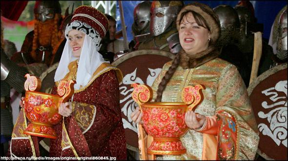 женщины в национальных костюмах с чашами медовухи встречают гостей фестиваля